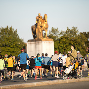 A spectator cheers on runners in the 2013 Cherry Blossom 10-Mile Run. Scheduled to coincide with the National Cherry Blossom Festival in early spring, the race takes runners along the National Mall and by the famous cherry blossoms around the Tidal Basin. In the background is Memorial Bridge with its gold statues on the eastern end.