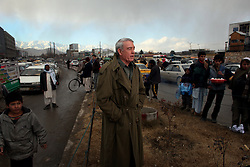 """In the Afghan capital, Kabul, journalist Dan Rather prepares to deliver a """"stand-up"""" televised report before cameras from his """"Dan Rather Reports"""" television program in late December 2008."""