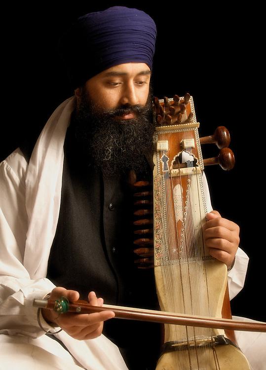 Punjab Singh playing a sarangi.