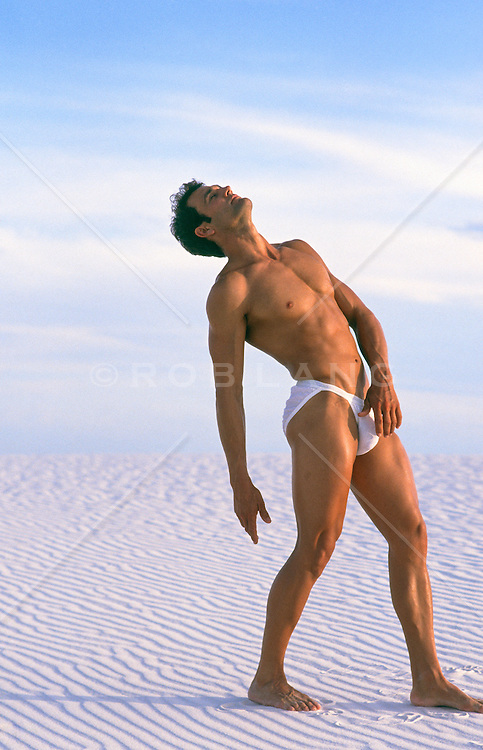 sexy man in bikini briefs posing in the sand dunes of White Sands, New Mexico