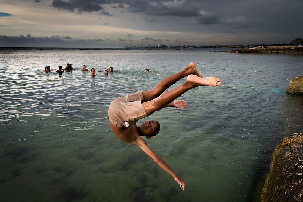 A boy flips into the water at the Playa Jaimanitas on the western edge of Havana, Cuba.