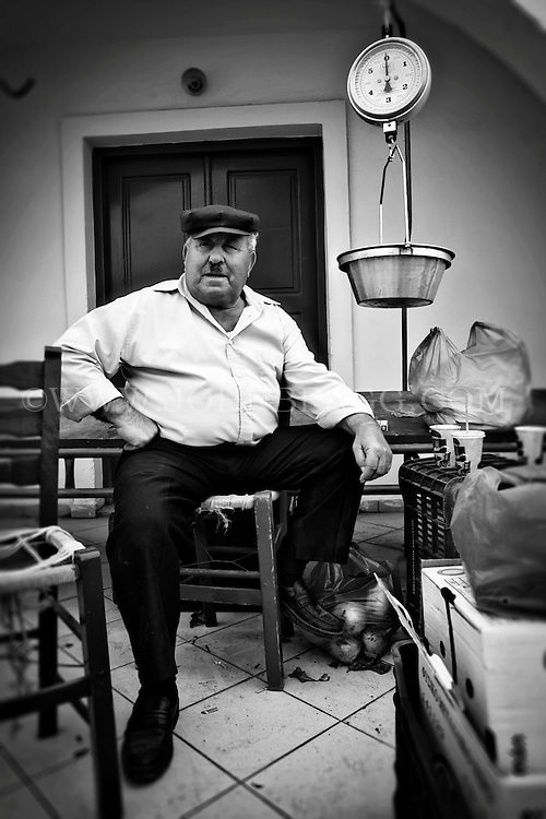 Black and white photo of an older man at a market in Santorini, Greece.