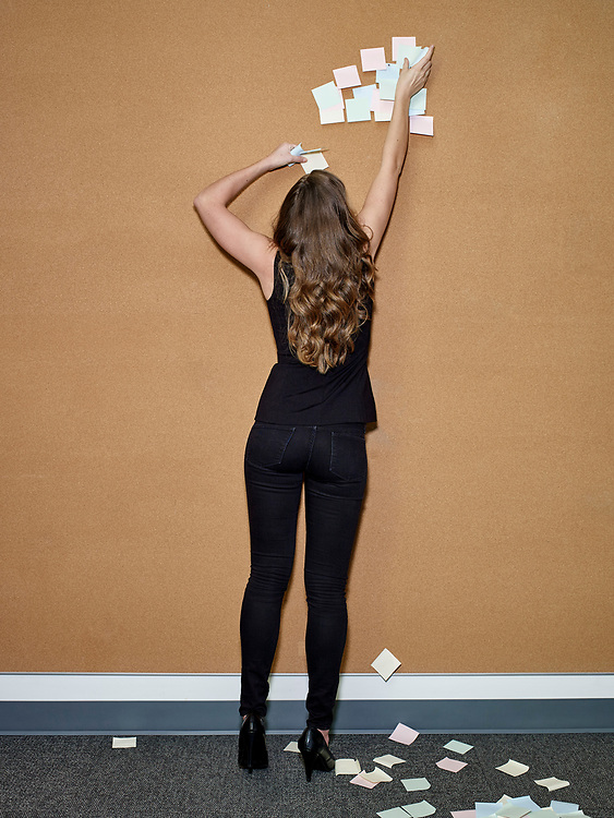 Woman removing post-it notes from cork wall in office setting