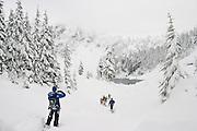 A group of hikers snowshoe through deep snow towards Boulder Lake, Glacier Peak Wilderness, Washington.