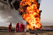 Boots and Coots prepare to attack their first oil well fire in the Rumaila Oil Field after a delay of a week due to security, sandstorms, and bureaucracy problems. They are taking a close look while shielding themselves with metal roofing pieces to block the intense heat of the fire. Rumaila is one of Iraq's biggest oil fields with five billion barrels in reserve. Many of the wells are 10,000 feet deep and produce huge volumes of oil and gas under tremendous pressure, which makes capping them very difficult and dangerous. Rumaila is also spelled Rumeilah.