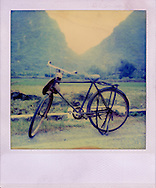 """Polaroid SX 70 picture of a bicycle along the road. It looks like bicycle style in 1940""""s. Guangxi province, China, Asia."""