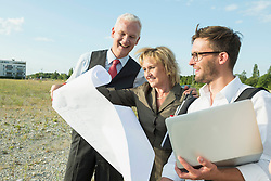 Three smiling people at development area