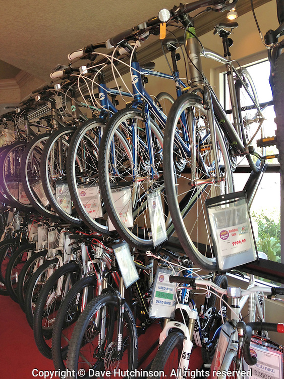 Two rows of bicycles for sale neatly lined up on a display rack in a bike store.