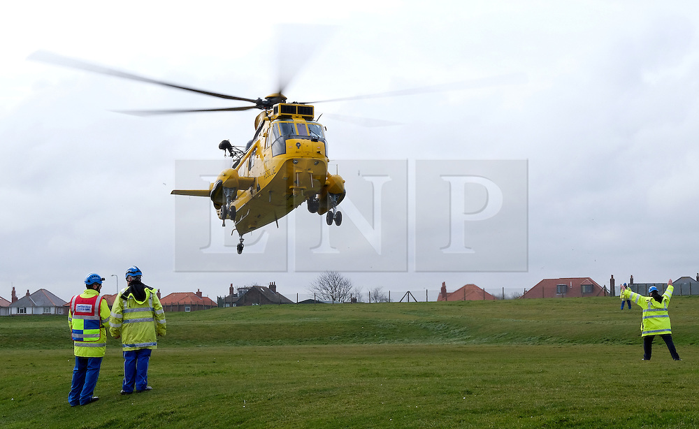 © Licensed to London News Pictures. <br /> 15/03/2015. <br /> <br /> Whitby, United Kingdom<br /> <br /> A Royal Air Force Sea king Search and Rescue helicopter, call sign Rescue 128 lands in front of members of the Coastguard in Whitby in North Yorkshire. This was the final flight for this helicopter and as a way to say goodbye to members of the public it landed in Whitby.<br /> <br /> Photo credit : Ian Forsyth/LNP
