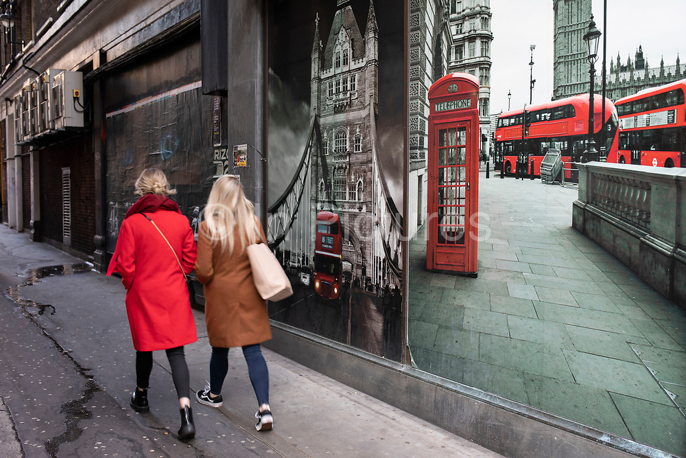 Woman wearing a red coat walking down an alley off Oxford Street past a poster depicting Tower Bridge and the iconic Routemaster bus and telephone box on 21st January 2020 in London, England, United Kingdom. Oxford Street is a major road in the West End of London. It is Europes busiest shopping street, with around half a million daily visitors, and has approximately 300 shops.