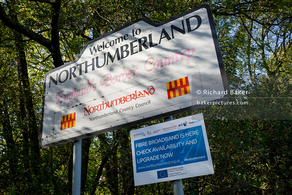 A Welcome to Northumberland road sign along with a fibre broadband notice, on the Northumbrian and County Durham border, near the Northumbrian village of Blanchland, on 29th September 2017, in Blanchland, Northumberland, England. Blanchland is a village in Northumberland, England, on the County Durham boundary. The population of the Civil Parish at the 2011 census was 135. Blanchland was formed out of the medieval Blanchland Abbey property by Nathaniel Crew, 3rd Baron Crew, the Bishop of Durham, 1674-1722. It is a conservation village, largely built of stone from the remains of the 12th-century Abbey. It features picturesque houses, set against a backdrop of deep woods and open moors. Set beside the river in a wooded section of the Derwent valley, Blanchland is an attractive small village in the North Pennines Area of Outstanding Natural Beauty.