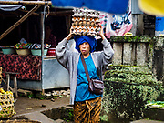 04 AUGUST 2017 - PAYANGAN, BALI, INDONESIA: An egg vender walks through the local market in Payangan, about 45 minutes from Ubud. Bali's local markets are open on an every three day rotating schedule because venders travel from town to town. Before modern refrigeration and convenience stores became common place on Bali, markets were thriving community gatherings. Fewer people shop at markets now as more and more consumers go to convenience stores and more families have refrigerators.      PHOTO BY JACK KURTZ