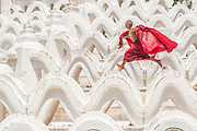 A novice monk runs and jumps along the structures at Mya Thein Tan Pagoda in Mingun which is near Mandalay, Myanmar.