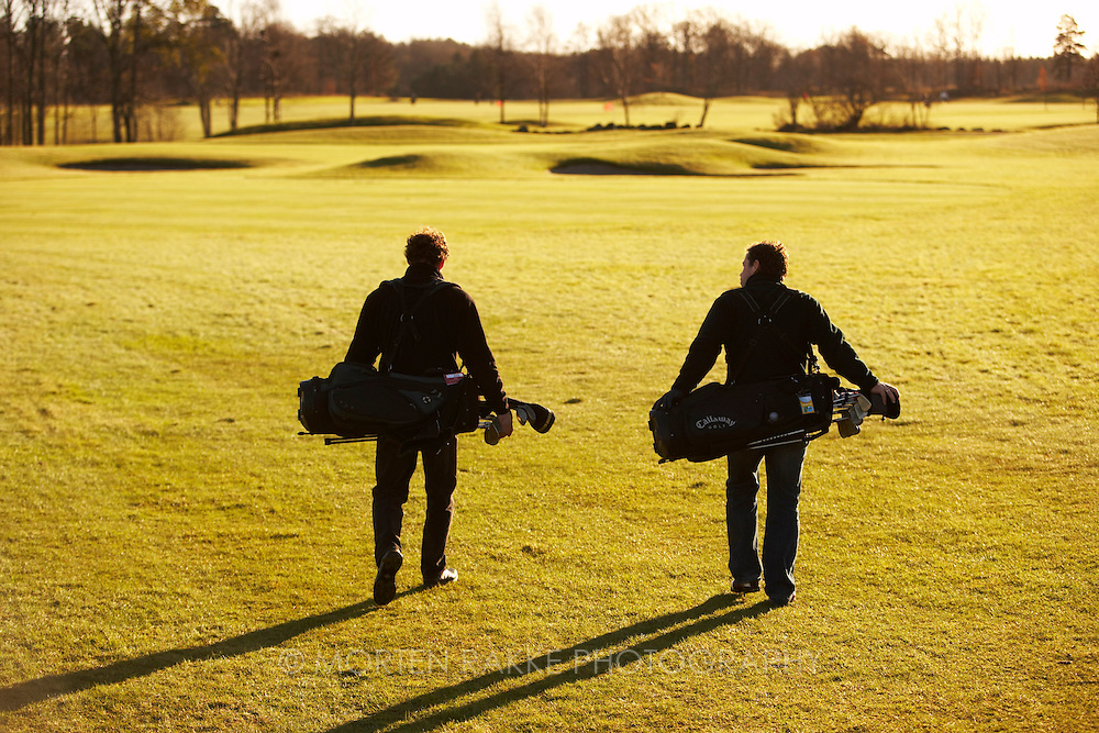 Golfers talking about their game, walking on fairway, rear view.