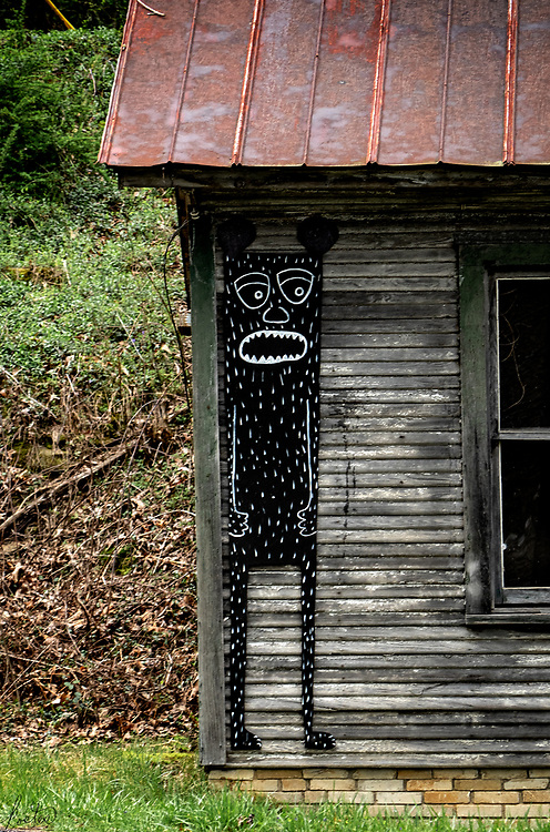 A sculpture of a strange creature on a building next to the Spruce Pine Post Office