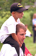 Son riding on dad's shoulders ages 30 and 5 at Memorial day service.  St Paul  Minnesota USA