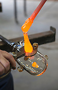 Glassblower cuts molten glass with a hand tool