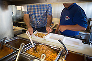 Owner Francisco Rodriguez (left) and Bernardo Garcia add rice, beans, and other toppings to an order of nacho fries at Taqueria Las Vegas in Milpitas, Calif., on Sept. 20, 2012.  Photo by Stan Olszewski/SOSKIphoto.