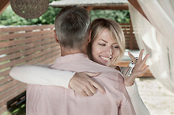 Couple married hugging woman holding keys smiling