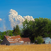 Smoke from a massive forest fire near Yellowstone National Park billows over old ranch building in the Gallatin Valley near Bozeman, Montana.