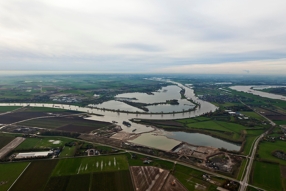 Nederland, Gelderland, Gemeente Maasdriel, 15-11-2010. Heerewaarden met  Heerewaardese afsluitdijk. Deze dijk scheidt de rivieren Maas en Waal (rechts). Onder in beeld Over de Maas waar de uiterwaarden worden uitgegraven door een zandzuiger. Het doel is zandwinning, natuurontwikkeling en rivierverruiming..Heerewaarden with Heerewaardese dam. This dike separates the rivers Maas and Waal (right). At the bottom the Meuse floodplains is excavated by a suction dredger.  Mining the sand creates new nature and 'room for the river'.luchtfoto (toeslag), aerial photo (additional fee required).foto/photo Siebe Swart