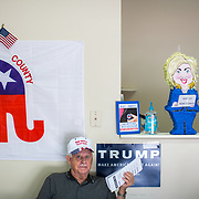 """September 14, 2016 - Sylva, North Carolina, United States: A pinata of Democratic presidential candidate Hillary Clinton sits on a counter above office manager, Clark Sheffield, inside the Jackson County GOP headquarters. The replica of the former Secretary of State is holding a laptop that reads """"What top secret emails?"""".  (Logan R Cyrus/ Polaris)"""
