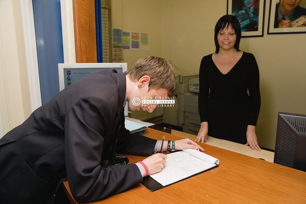 Secondary school student signing in at school reception,