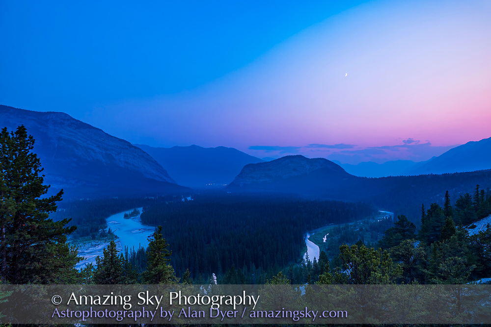 Blue hour twilight with a waxing crescent Moon, over the Bow Valley, Banff, Alberta, on an evening with the air filled with smoke from B.C. forest fires to the west, muting the colours and clarity. <br /> <br /> This is from the Hoodoos Viewpoint trail on Tunnel Mountain Drive, looking back toward Banff. The lights of the Banff Springs Hotel are in the distance at left. The Bow River winds below. Tunnel Mountain is at centre with Sulphur Mountain to the left. The Hoodoos are at the bottom of the frame. <br /> <br /> This is a single image with the Canon EOS Ra and 15-35mm RF lens at 20mm.