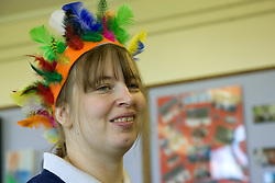 Portrait of young woman Day Service user with learning disability wearing an Indian feather headdress,