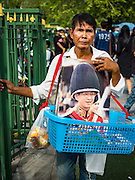 15 OCTOBER 2016 - BANGKOK, THAILAND: A man sells portraits of Bhumibol Adulyadej, the King of Thailand, on the street in front of the Grand Palace in Bangkok. King Bhumibol Adulyadej died Oct. 13, 2016. He was 88. His death comes after a period of failing health. With the king's death, the world's longest-reigning monarch is Queen Elizabeth II, who ascended to the British throne in 1952. Bhumibol Adulyadej, was born in Cambridge, MA, on 5 December 1927. He was the ninth monarch of Thailand from the Chakri Dynasty and is known as Rama IX. He became King on June 9, 1946 and served as King of Thailand for 70 years, 126 days. He was, at the time of his death, the world's longest-serving head of state and the longest-reigning monarch in Thai history.      PHOTO BY JACK KURTZ