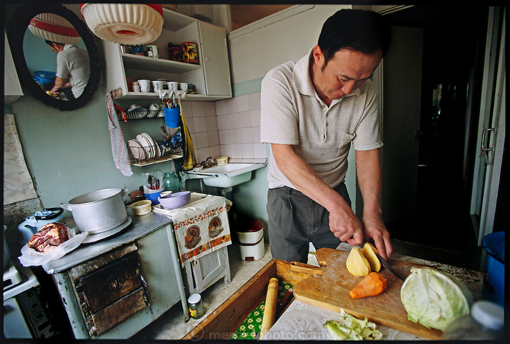 (MODEL RELEASED IMAGE).Regzen Batsuuri slices up squash, carrots, and cabbage in the small kitchen of his Mongolian home which his family of four shares with two other families. Hungry Planet: What the World Eats (p. 232). The Batsuuri family of Ulaanbaatar, Mongolia, is one of the thirty families featured, with a weeks' worth of food, in the book Hungry Planet: What the World Eats.