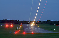 The lights from a single-engine airplane streak across the sky as the plane takes off from Randall Airport on the eveining of Aug. 19, 2013.