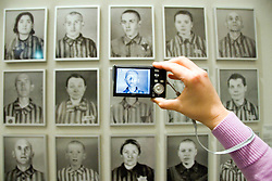 Visitor photographing exhibit of concentation camp vicitms with digital camera at German History Museum in Berlin