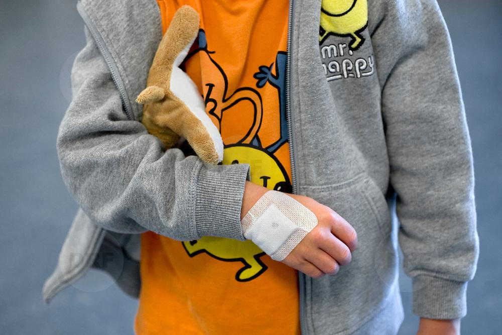 Nederland Rotterdam 25-08-2009 20090825 Foto: David Rozing ..Serie over zorgsector, Ikazia Ziekenhuis Rotterdam. Jong kind heeft als troost een verband gekregen, het kind is zojuist besneden dus het verband is voor de show.  Young child boy with bandages, these are fake, the boy has been circumciced and the fake bandage are meant to cheer him up. Holland, The Netherlands, dutch, Pays Bas, Europe, verband, verbonden, hoofdwond, gaas, gaasje, wondbedekker, verbandgaas, verbandgazen, vulnerable, knuffel, smiley, smileys, tegenstelling, contrast, positief blijven, positiviteit, ventje..Foto: David Rozing genezen, genezing, ziekte bestrijding,, onherkenbaar, onherkenbare,unrecognisable,,ziektekosten,,zorgverlening
