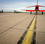 Engineering ground staff of the Red Arrows, Britain's RAF aerobatic team during winter training turnaround. <br /> <br /> Wearing military green overalls and fluorescent tabard, the 'line' engineers from the elite team come to the aid of an arrived Hawk jet after another training flight at RAF Scampton, their UK base. The men are members of the team's support ground crew (called the Blues because of their distinctive blue overalls worn at summer air shows). The team's support ground crew who outnumber the pilots 8:1 and without them, the Red Arrows couldn't fly. Eleven trades are imported from some sixty that the RAF employs and teaches.