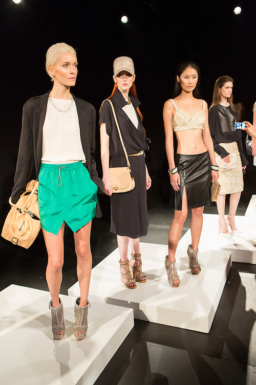 Models pose on platforms as guests circulate around them at the Monika Chiang show at Spring 2013 Fashion Week in New York.