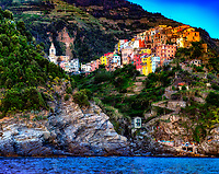 """""""The bell tower of the church of San Pietro rises above Corniglia""""…<br /> <br /> I began my daily journey at the northern most town of Monterosso and took the train to the southernmost town of Riomaggiore. I sailed up the coast photographing each Cinque Terre town along the way aboard the Angelina Dada. Upon arriving back home in Monterosso, soft light illuminated the sky and azure sea of the Mediterranean convincing me to sail all the way back to Riomaggiore with my gracious guides Claudio and Eddie of """"Cinque Terre dal Mare"""" sailing excursions. We arrived just in time for a perfect sunset. After a nice dinner...I caught the last train at midnight back home to Monterosso. A very long day, but worth every minute!  This panorama image of Corniglia, the only Cinque Terre town not directly on the sea…was taken on the journey back to Riomaggiore at dusk.  The tiny village seems snuggled into the Cliffside soaking up the last bit of sunlight before nightfall.  The ancient campanile of the church of Saint Peter, which was built in 1334, begins to peer over the cliff in the upper part of Corniglia."""