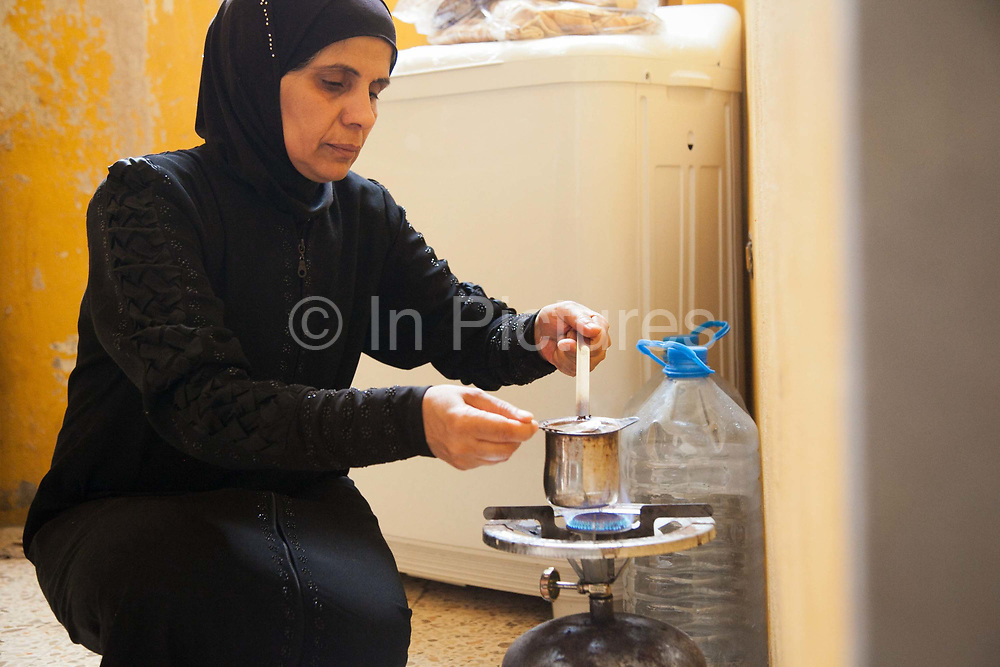 Delal makes coffee on her gas cooker in her temporary home in Shatila. Delal walks along the narrow alleys to her temporary home in Shatila. She is a Palestinian from Damascus and now lives as a refugee in Shatila, a Palestinain camp in Beirut. She lives in Shatila with her extended family after they had to flee the war in Syria.