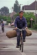 A Hungarian man cycles on the road with a large sack of produce  in a village in rural Hungary, on 18th June 1990, in Hungary.
