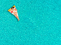 Aerial view of woman floating on inflatable pizza mattress, relaxing and smiling.