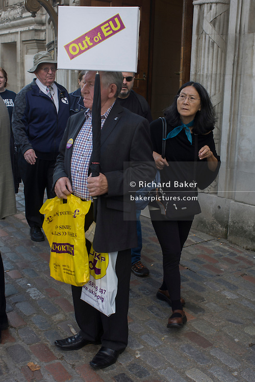 A UKIP (UK Independence Party) member holds an anti-EU placard to the interest of passers-by outside their party conference in Westminster, central London.