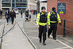 © Licensed to London News Pictures; 06/03/2021; Bristol, UK. Police patrol Bristol Harbourside on Saturday as people take exercise during lockdown in the covid coronavirus pandemic, and advise groups of people sitting down to move on. People are allowed to exercise with their household or bubble or with one person from another household, but not to sit down and chat. Photo credit: Simon Chapman/LNP.