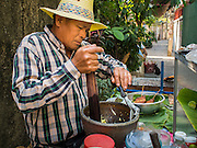 06 FEBRUARY 2015 - BANGKOK, THAILAND: A street food vendor makes spicy mango salad on his cart in the neighborhood around Santa Cruz Church in the Thonburi section of Bangkok. Now the neighborhood around the church is known for the Thai adaptation of Portuguese cakes baked in the neighborhood. Several hundred Siamese (Thai) Buddhists converted to Catholicism in the 1770s. Some of the families started baking the cakes. When the Siamese Empire in Ayutthaya was sacked by the Burmese, the Portuguese and Thai Catholics fled to Thonburi, in what is now Bangkok. The Portuguese established a Catholic church near the new Siamese capital. There are still a large number of Thai Catholics living in the neighborhood around the church.       PHOTO BY JACK KURTZ