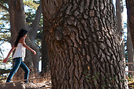 A Lebanese woman, a Christian cross attached to her bracelet, walks in an old growth grove of cedars near the Lebanese town of Bcharre.
