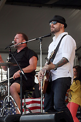 29 April 2012. New Orleans, Louisiana,  USA. <br /> New Orleans Jazz and Heritage Festival. <br /> Fred LeBlanc (l), lead singer and drummer for the band Cowboy Mouth with Matt Jones.<br /> Photo; Charlie Varley/varleypix.com