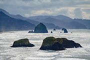 Pounding surf eroded bluffs to expose Bird Rocks and Haystack Rock (behind) at Cannon Beach, seen from Ecola State Park, on the Oregon coast, USA. Haystack Rock, a 235-foot high sea stack, is part of the Tolovana Beach State Recreation Site, along the Pacific Ocean seaboard.