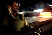 An armed member of the AVCC, (Anti-Violence Crime Cell) a special police unit mostly involved in anti-terrorism operations and kidnap cases in the city of Karachi, is riding in a police van in the city on their way to a night raid aimed at freeing a hostage and arresting the offenders.