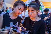 20 MAY 2014 - BANGKOK, THAILAND: A Thai women light candles during a vigil against martial law. About 200 Thais gathered at the Bangkok Art and Culture Centre in central Bangkok to protest the army's decision to impose martial law.   PHOTO BY JACK KURTZ