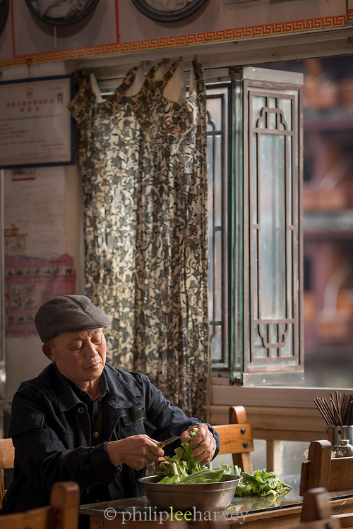 Mature male restaurant worker occupied with cutting vegetables, Fenghuang, Hunan Province, China