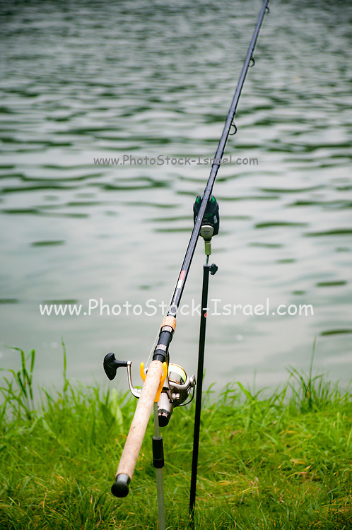 baited Fishing rod on a river bank